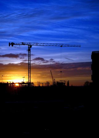 Cranes and construction site silhouette against setting (or rising) sun Banque d'images