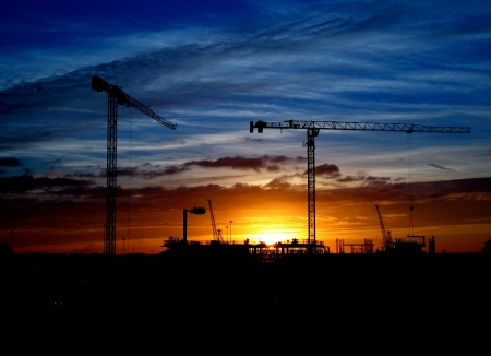 Cranes and construction site silhouette against setting (or rising) sun photo