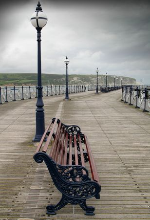 british weather: Lonely english summer. A view of a solitary bench on a pier with depressing overhead clouds