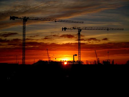 manufacturer: Cranes and construction site silhouette against setting (or rising) sun Stock Photo