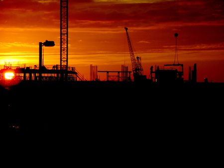 Cranes and construction site silhouette against setting (or rising) sun Stock Photo