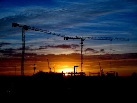 Cranes and construction site silhouette against blue and orange sky and setting (or rising) sun