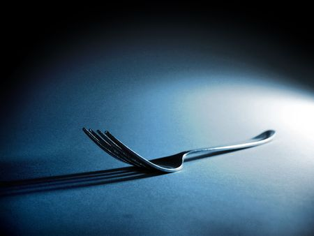 contrasty: Fork in contrasty light on textured background Stock Photo