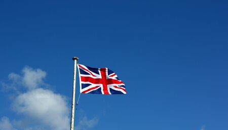flagpoles: Union Flag on a windy day. This is the flag, generally regarded, to represent the peoples of England, Scotland, Wales and Northern Ireland. The image may show the effect of the wind at full size. Stock Photo