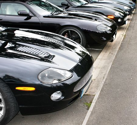 Fronts of a row of dark shiny luxury cars photo
