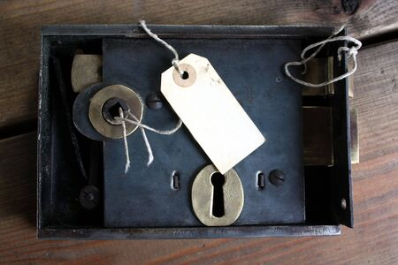 Old fashined door lock and tag label on locksmiths workbench