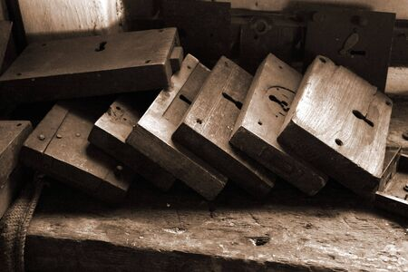 Layers of old fashioned locks on a locksmiths workbench in a sepia style