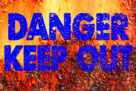 DANGER KEEP OUT in blue spray paint style on decayed rusty metal sign photo