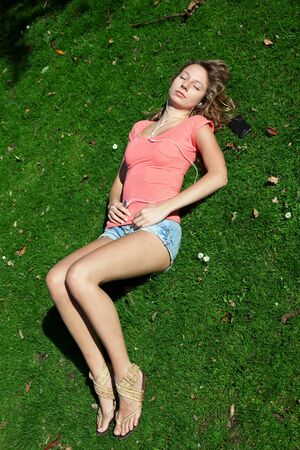 Beutiful Woman relaxing in park and listening to music on a sunny day photo