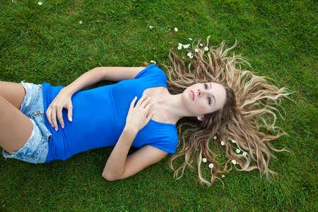 Young beautiful woman lying in park photo