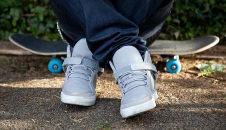 ni�o en patines: Hombre sentado sobre su patineta Foto de archivo