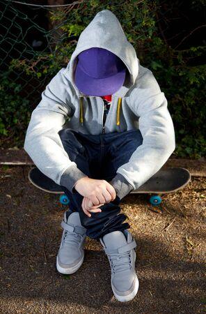 assis par terre: Jeune patineur couvrant le visage avec un chapeau et un capuchon