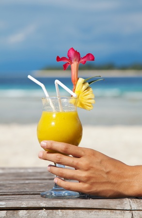 Woman holding a cocktail on a tropical beach photo