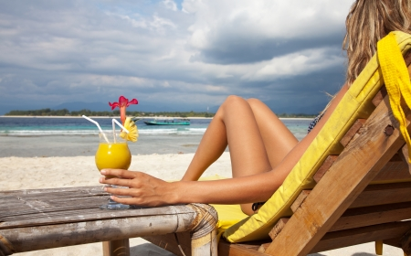 Woman enjoying a cocktail on a tropical beach