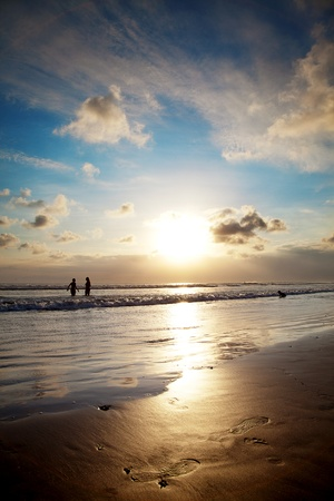 Golden sunset, blue sky and footsteps in sand, Bali Indonesia Stock Photo