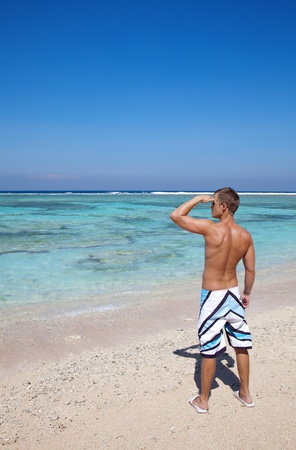 Young man looking into distance on a beautiful beach