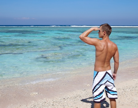 Young man looking into distance on a beautiful beach photo