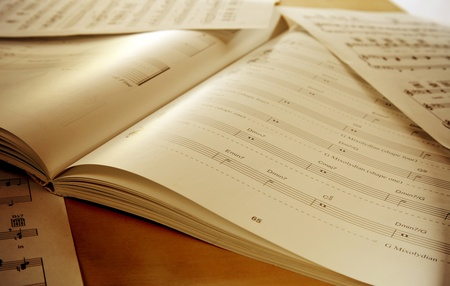Book and papers with music notes on table photo