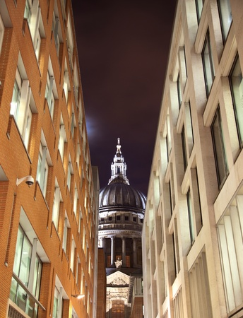 St Paul's cathedral seen through a narrow street with business offices buildings photo