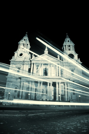 Vintage look of St Pauls cathedral with blurred bus trail at night photo
