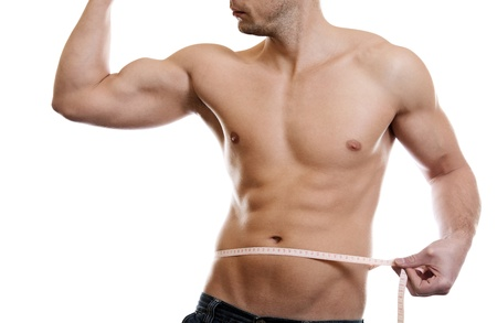 Muscular man measuring waist on white photo