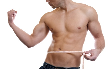 Muscular man measuring waist on white photo