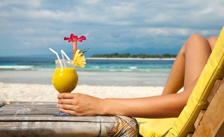strandstoel: Vrouw met een fruitcocktail op een tropisch strand Stockfoto