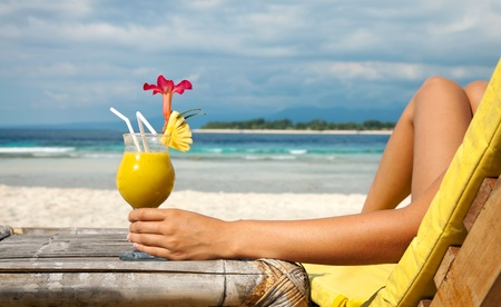 deckchair: Woman holding a fruit cocktail on a tropical beach