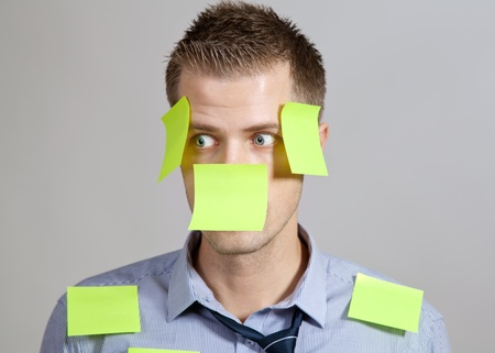 Confused businessman with post it notes on face and clothes photo