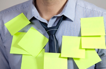 Businessman with plenty of post it notes photo