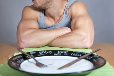 bodybuilder training: Muscular man sitting at the table with empty plate