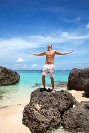 Muscular man enjoying paradise beach