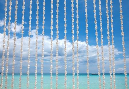 Exotic beacg behind a sea shell curtain photo