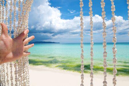 Paradise beach through a sea shell curtain photo