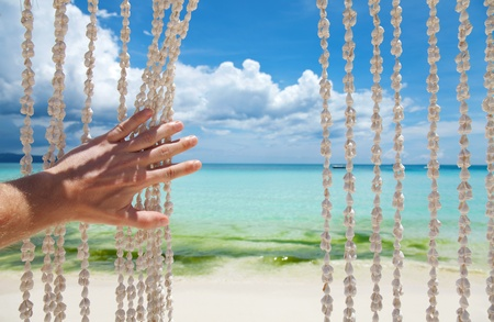Paradise beach through a sea shell curtain photo