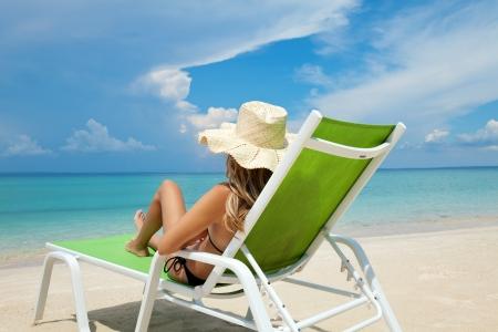 Mujer joven con sombrero de relajarse en una tumbona