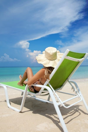 deckchair: Young woman with hat relaxing on a deck chair Stock Photo