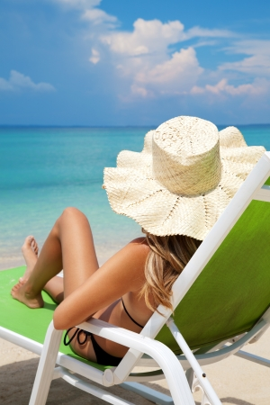 sunbathing: Young woman with hat relaxing on a deck chair Stock Photo