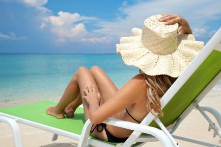 Mladá žena s kloboukem na dovolené na lehátku