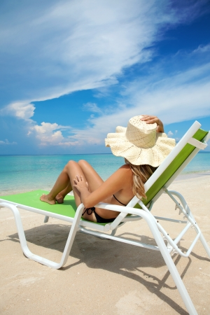 Young woman with hat relaxing on a deck chair photo
