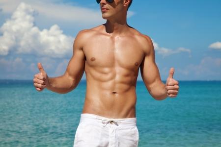hombres sin camisa: Hombre musculoso que muestran los pulgares para arriba en una playa