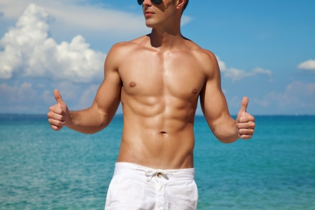 masculine: Muscular man showing thumbs up on a beach