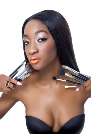 make up brushes: Beauty portrait of a young African beauty holding make up brushes