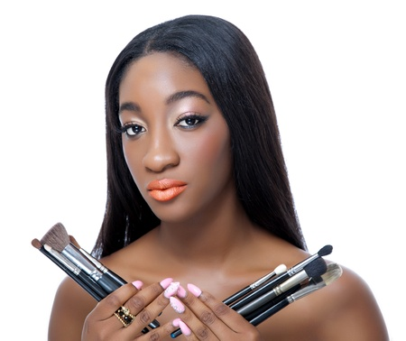 make up brushes: Portrait of an African beauty holding make up brushes