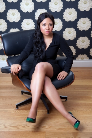 Businesswoman sitting on a leather chair with legs crossed photo