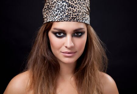 Young beauty with smokey eye makeup wearing a head scarf photo