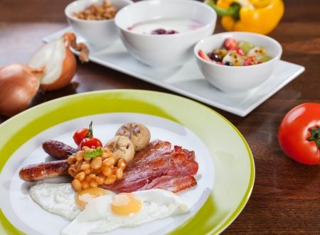 Full English breakfast with quail eggs and granola with yogurt photo