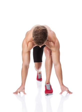 Muscular man in start position ready for the race photo