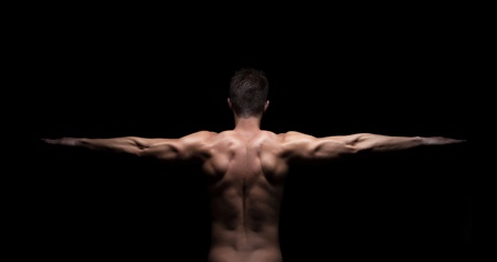 Rear view of a muscular man with arms streched out on black background photo