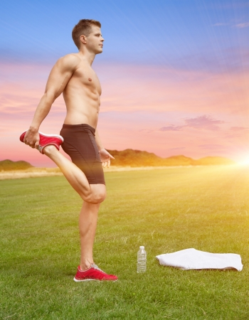 Muscular man stretching out in beautiful scenery photo